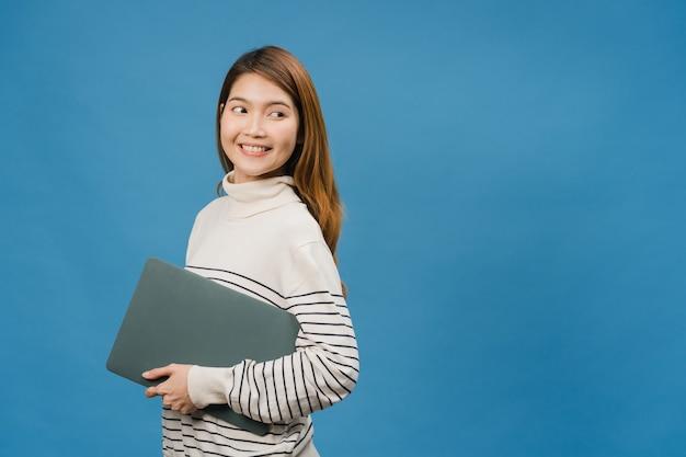 Jonge aziatische dame houdt laptop vast met positieve uitdrukking, glimlacht breed, gekleed in casual kleding en voelt zich gelukkig en staat geïsoleerd op blauwe muur