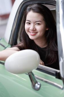 Jonge aziatische dame in een uitstekende auto
