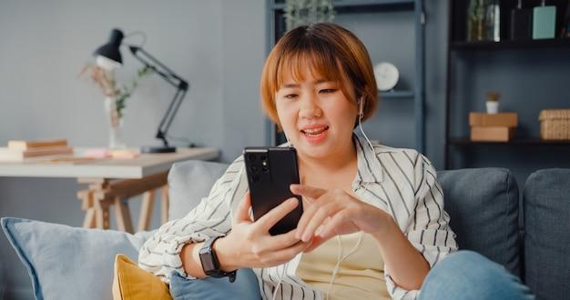 Jonge aziatische dame met behulp van slimme telefoon videogesprek praten met familie op de bank in de woonkamer thuis