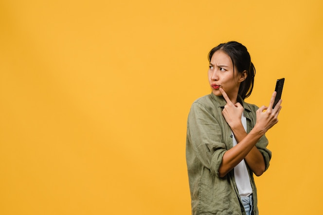 jonge aziatische dame met behulp van telefoon met positieve uitdrukking gekleed in casual doek op gele muur