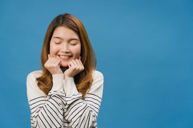 Jonge aziatische dame met positieve uitdrukking, glimlach breed, gekleed in vrijetijdskleding en sluit je ogen over de blauwe muur
