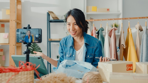 Jonge aziatische dame modeontwerper met behulp van mobiele telefoon ontvangen inkooporder en kleding in livestream tonen