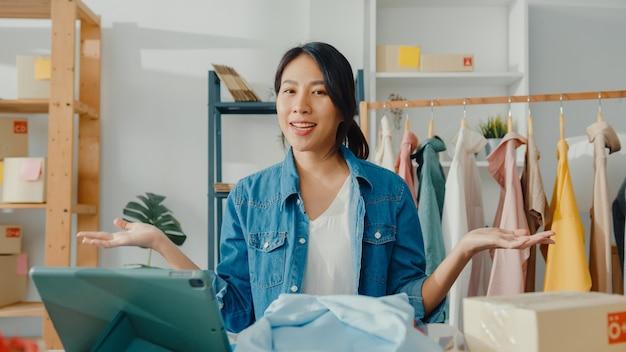 Jonge aziatische dame modeontwerper met behulp van mobiele telefoon ontvangen inkooporder en kleding in livestream tonen Gratis Foto