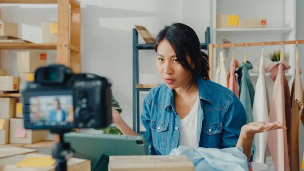 Jonge aziatische dame modeontwerper met behulp van mobiele telefoon ontvangen inkooporder en kleding tonen in live streaming