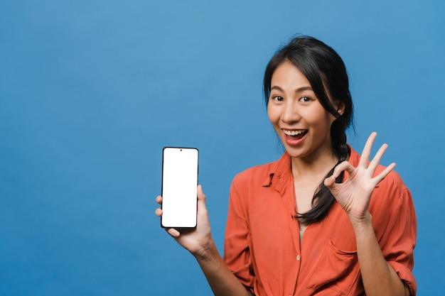 Jonge aziatische dame toont een leeg smartphonescherm met positieve uitdrukking, glimlacht breed, gekleed in casual kleding en voelt zich gelukkig op de blauwe muur. mobiele telefoon met wit scherm in vrouwelijke hand.