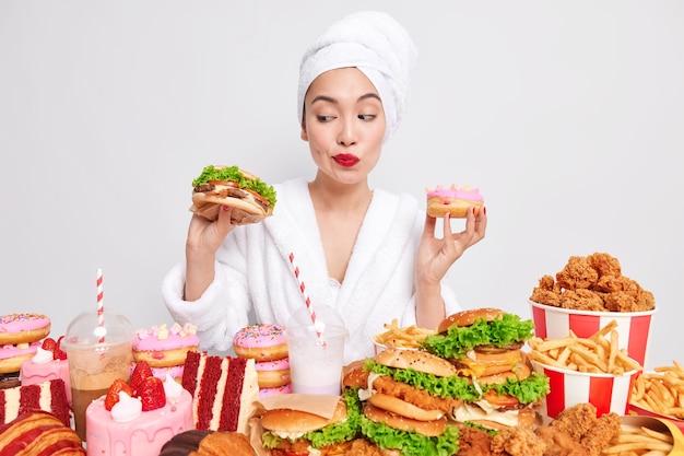 Jonge aziatische dame twijfelt tussen een hamburger en een donut
