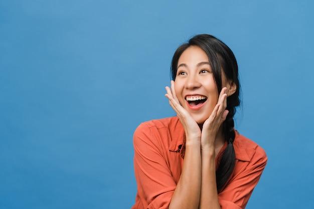 Jonge aziatische dame voelt geluk met positieve uitdrukking, vrolijke funky verrassing, gekleed in casual doek geïsoleerd op blauwe muur. gelukkige schattige blije vrouw verheugt zich over succes. gezichtsuitdrukking.