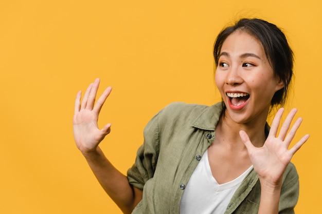 Jonge aziatische dame voelt geluk met positieve uitdrukking, vrolijke funky verrassing, gekleed in casual doek geïsoleerd op gele muur. gelukkige schattige blije vrouw verheugt zich over succes. gezichtsuitdrukking.