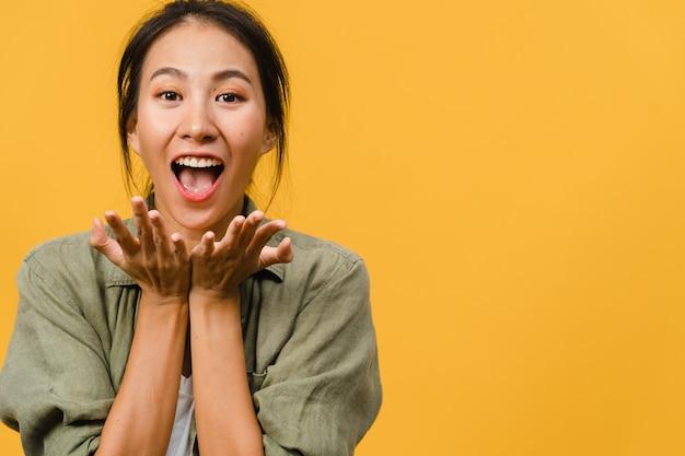 Jonge aziatische dame voelt geluk met positieve uitdrukking, vrolijke funky verrassing, gekleed in casual doek geïsoleerd op gele muur. gelukkige schattige blije vrouw verheugt zich over succes.