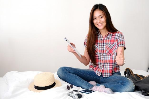 Jonge aziatische de holdingskaart en duim van de vrouwenreiziger omhoog terwijl het zitten op bed met het glimlachen gezicht