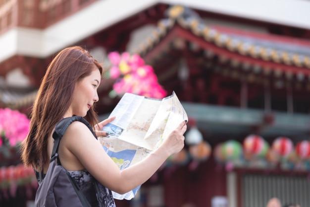 Jonge aziatische de holdingskaart van de vrouwenreiziger in chinatown, singapore