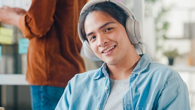 Jonge aziatische designer man luisteren naar muziek op de koptelefoon, camera kijken en glimlachend in moderne kantoren. groep jonge studenten in slimme vrijetijdskleding op de campus. collega teamwerk concept.