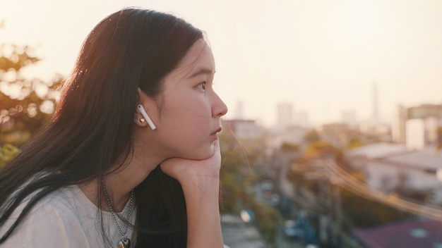 Jonge aziatische duizendjarige gen z vrouw die zich bij verveeld dak bevinden en cityscape bekijken terwijl het luisteren aan muziek