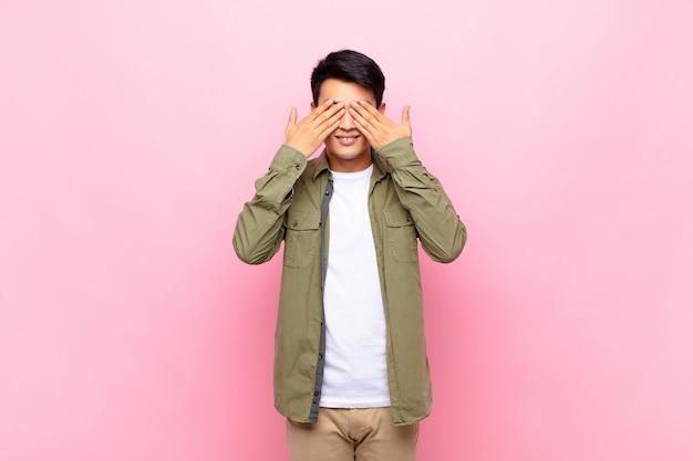Jonge aziatische en mens die gelukkig glimlacht voelt, ogen behandelt met beide handen en op ongelooflijke verrassing over kleurenmuur wacht