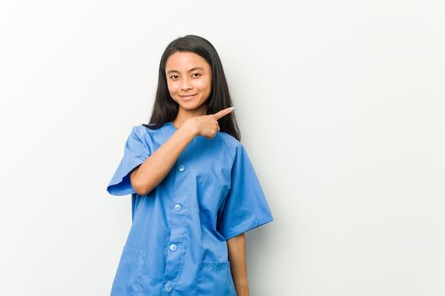 Jonge aziatische en verpleegstersvrouw die opzij glimlachen richten, die iets tonen op lege ruimte.