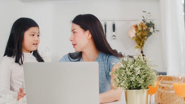 Jonge aziatische ernstige onderneemster, spanning, vermoeid en ziek terwijl thuis het werken aan laptop. jonge dochter die haar moeder troost die hard in moderne keuken bij huis in de ochtend werkt.
