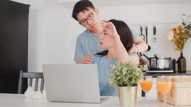 Jonge aziatische ernstige onderneemster, spanning, vermoeid en ziek terwijl thuis het werken aan laptop. man geeft haar glas water terwijl hij 's ochtends thuis hard aan het werk is in de moderne keuken.