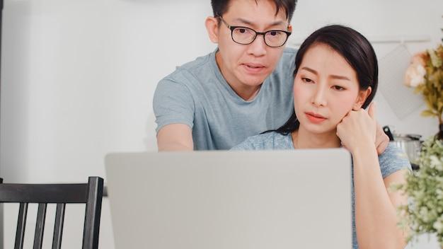 Jonge aziatische ernstige onderneemster, spanning, vermoeid en ziek terwijl thuis het werken aan laptop. man troost haar terwijl hij 's ochtends hard aan het werk is in de moderne keuken.