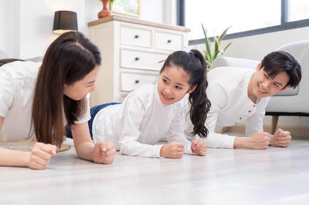 Jonge aziatische familie die thuis samen oefening doet