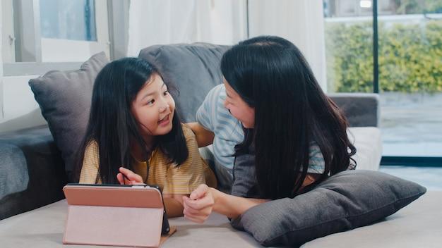 Jonge aziatische familie en dochter gelukkige thuis gebruikende tablet. de japanse moeder ontspant met meisje het letten op film liggend op bank in woonkamer bij huis. grappige moeder en lief kind hebben plezier.