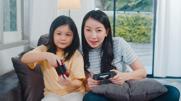 Jonge aziatische familie en dochter spelen games thuis. koreaanse moeder met meisje die bedieningshendel grappig gelukkig ogenblik samen op bank in woonkamer gebruiken bij huis. grappige moeder en lief kind hebben plezier