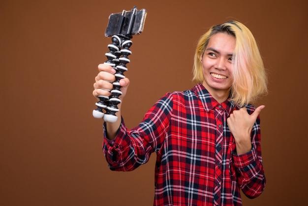 Jonge aziatische filipijnse man influencer vloggen in studio