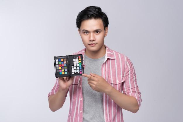 Jonge aziatische fotograaf die een kleurenkaart vasthoudt terwijl hij in de studio werkt