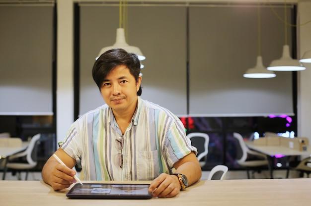 Jonge aziatische freelance ontwerper glimlacht terwijl hij naar de camera kijkt tegen een modern kantoor.