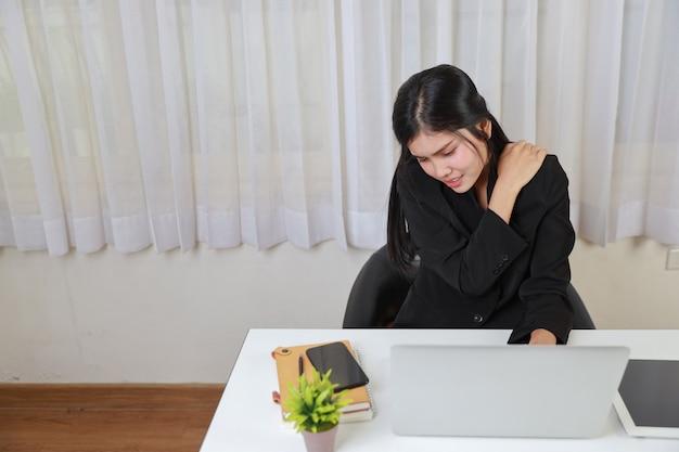 Jonge aziatische gestresste zakenvrouw die pijn voelt of problemen heeft met een deel van de schouder of nek van het lichaam, nadat ze te lang op de computer heeft gewerkt. kantoor syndroom concept