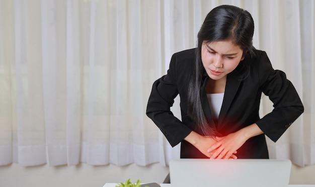 Jonge aziatische gestresste zakenvrouw die pijn voelt of problemen heeft met menstruatiepijn of buikpijn tijdens het werken op de computer. kantoor syndroom concept