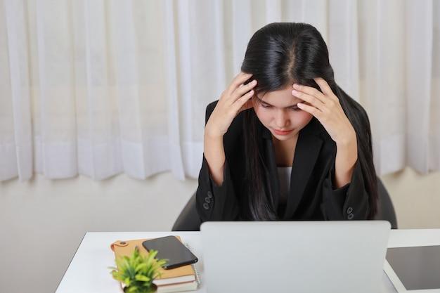 Jonge aziatische gestresste zakenvrouw die problemen heeft of pijn voelt bij het aanraken van tempels, lijdt aan hoofdpijn of migraine nadat ze te lang op de computer heeft gewerkt. kantoor syndroom concept
