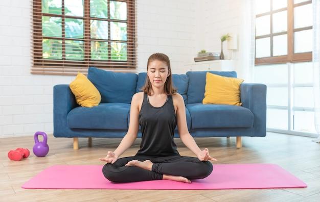 Jonge aziatische gezonde vrouw in sportkleding thuis trainen, oefenen, passen, yoga doen. thuis sport fitness concept