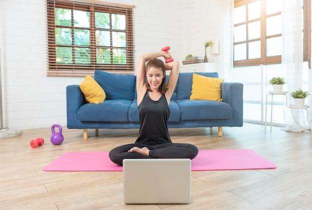 Jonge aziatische gezonde vrouw in sportkleding training thuis, oefenen, passen, yoga doen. thuis sport fitness concept