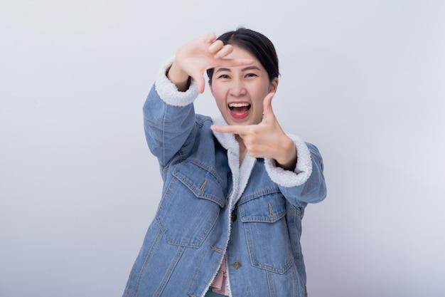 Jonge aziatische glimlachende opgewekte vrouw die haar hand met uitdrukking tonen die verrast en verbaasd voelen, positief gelukkig kaukasisch meisje die blauw vrijetijdskledingsportret dragen
