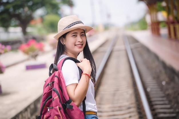 Jonge aziatische gril die bij station vóór reis lopen. werk en reizen concept.