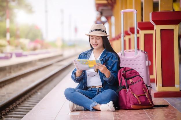 Jonge aziatische gril die bij station vóór reis lopen