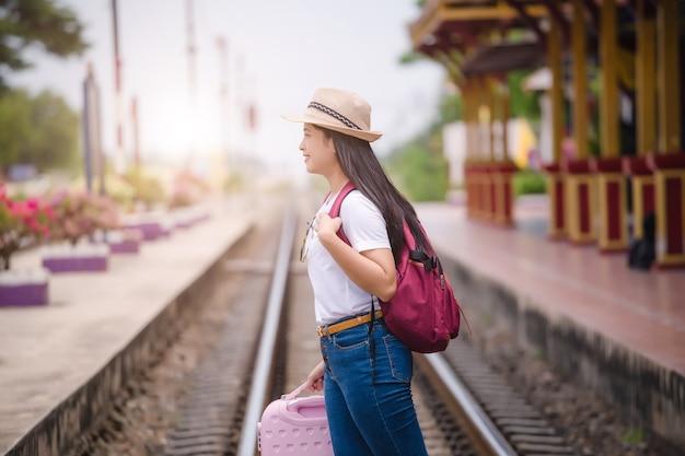 Jonge aziatische gril die bij treinstation vóór reis loopt. werk en reizen concept.