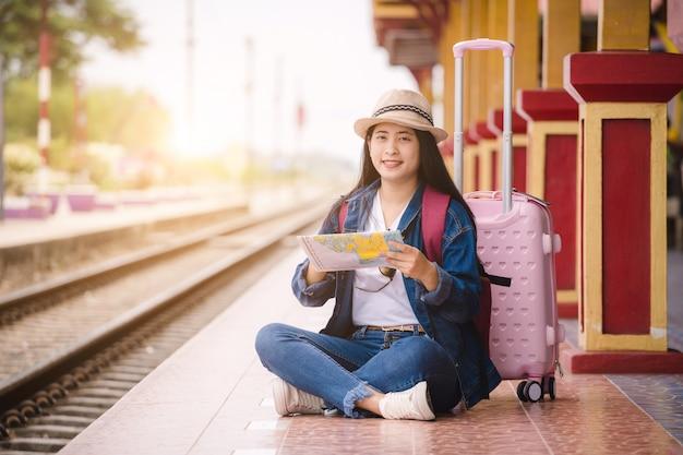 Jonge aziatische gril die de kaart houdt en bij station vóór reis zit. werk en reizen concept.