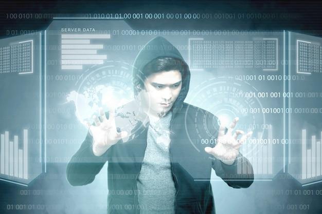 Jonge aziatische hacker in zwarte hoodie virtuele scherm aan te raken