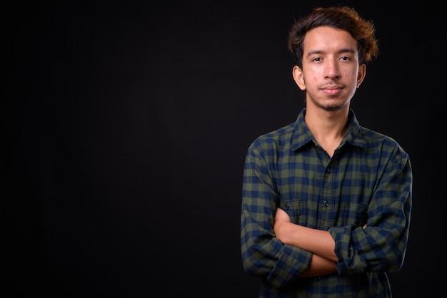 Jonge aziatische hipster man met krullend haar en acne tegen zwarte ruimte
