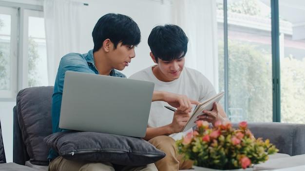 Jonge aziatische homo paar werkende laptop bij modern huis. azië lgbtq + mannen gelukkig ontspannen plezier met behulp van computer en het analyseren van hun financiën op internet samen liggend bank in de woonkamer in huis.