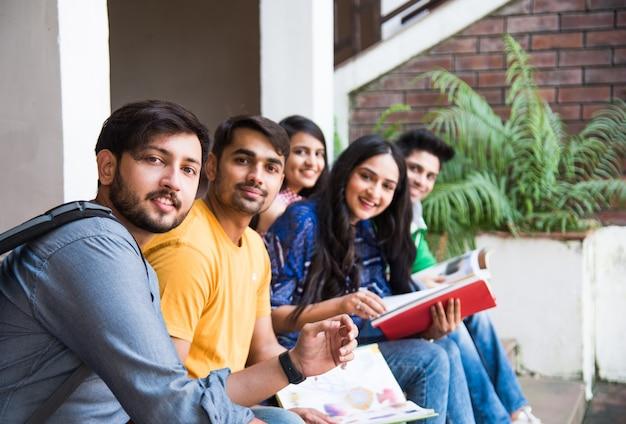 Jonge aziatische indiase studenten die boeken lezen, op laptop studeren, zich voorbereiden op een examen of aan een groepsproject werken terwijl ze op gras, trap of trappen van de universiteitscampus zitten