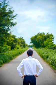 Jonge aziatische / indische jongen die zich op de weg bevindt