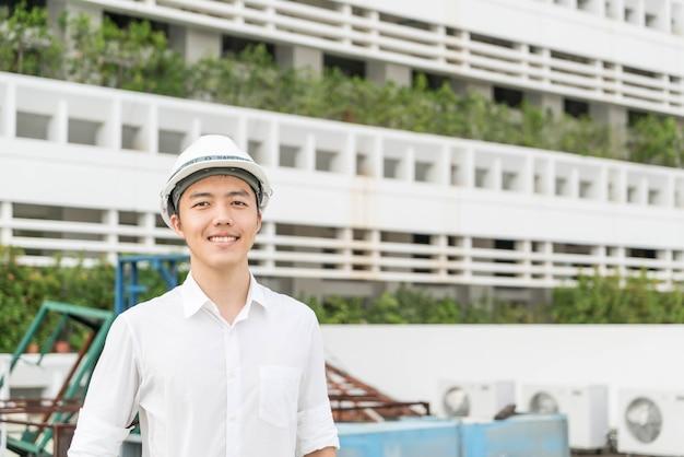 Jonge aziatische ingenieur met witte veiligheids harde helm
