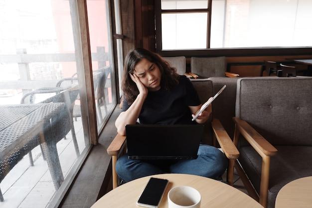 Jonge aziatische jonge vrouw werkt online met laptop op kantoor. ze houdt een tablet vast en is serieus over informatie op internet voor thuiswerk. zakenvrouw werken met technologie concept.