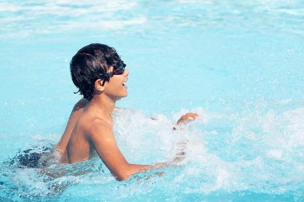 Jonge aziatische jongen die, en in het water speelt lacht speelt