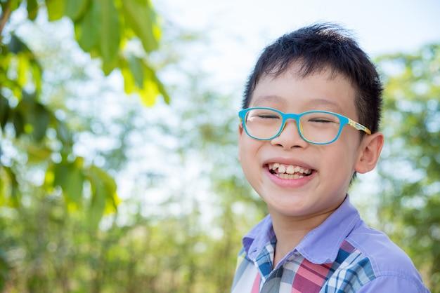 Jonge aziatische jongen die in park glimlacht