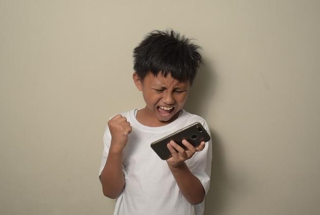 Jonge aziatische jongen die smartphone gebruikt en naar het scherm kijkt, bang in shock met een verrassingsgezicht