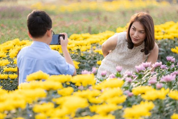 Jonge aziatische jongen die smartphone gebruikt om foto's te maken voor zijn moeder in tropische bloementuin, concept voor reizen als toerisme op landbouwgebied.