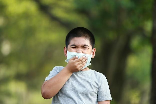 Jonge aziatische jongen, draag een masker ter bescherming tegen stof pm 2.5 en ziektekiemen